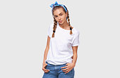istock Charming beautiful young woman wearing white t-shirt, blue headband with hands in the pockets, looking to the camera, isolated over white studio background 1135295862