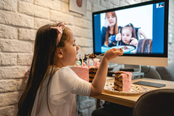 Charmante Geburtstag Mädchen essen Geburtstagstorte, während im Gespräch mit ihrer Familie über Video Anruf App in Zu hause Isolation – Foto