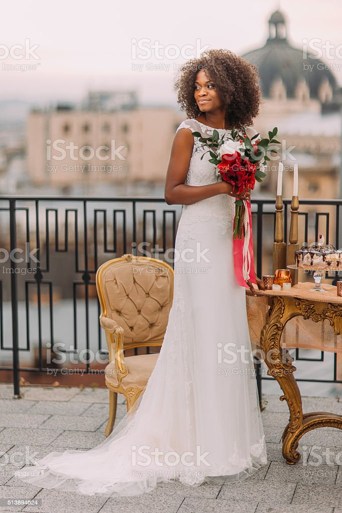 Charming black bride with wedding bouquet in hands standing on stock photo