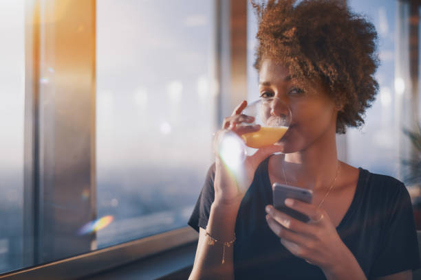 charming black girl drinking juice and chatting using smartphone - drinking juice stock photos and pictures