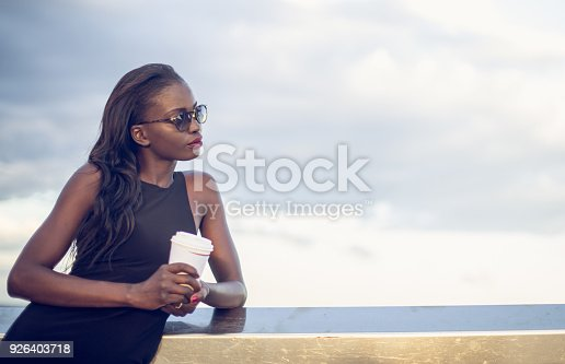 One woman, young and beautiful black woman, holding coffee cup.