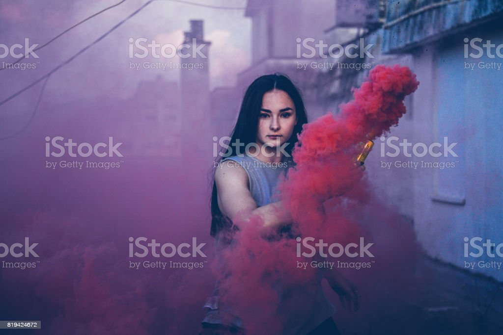 Charming Black-haired Girl Behind Pink Smoke stock photo