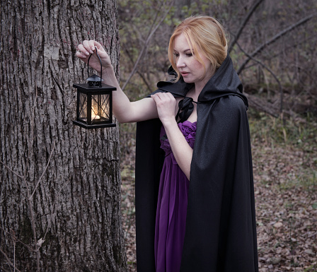 Charming blonde lady with lantern in the forest