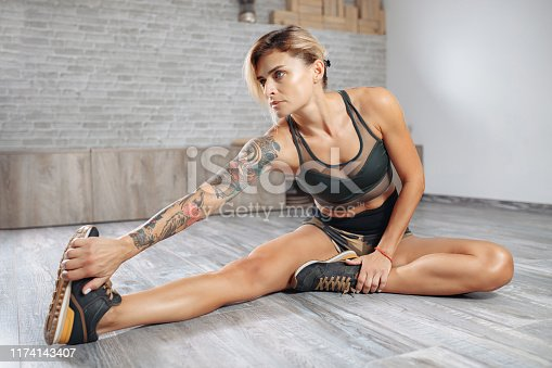 Charming blonde young slim woman in sports clothing stretching in gym. Female doing warmup stretching workout