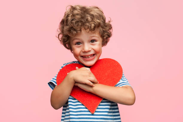 Charming boy posing with heart stock photo