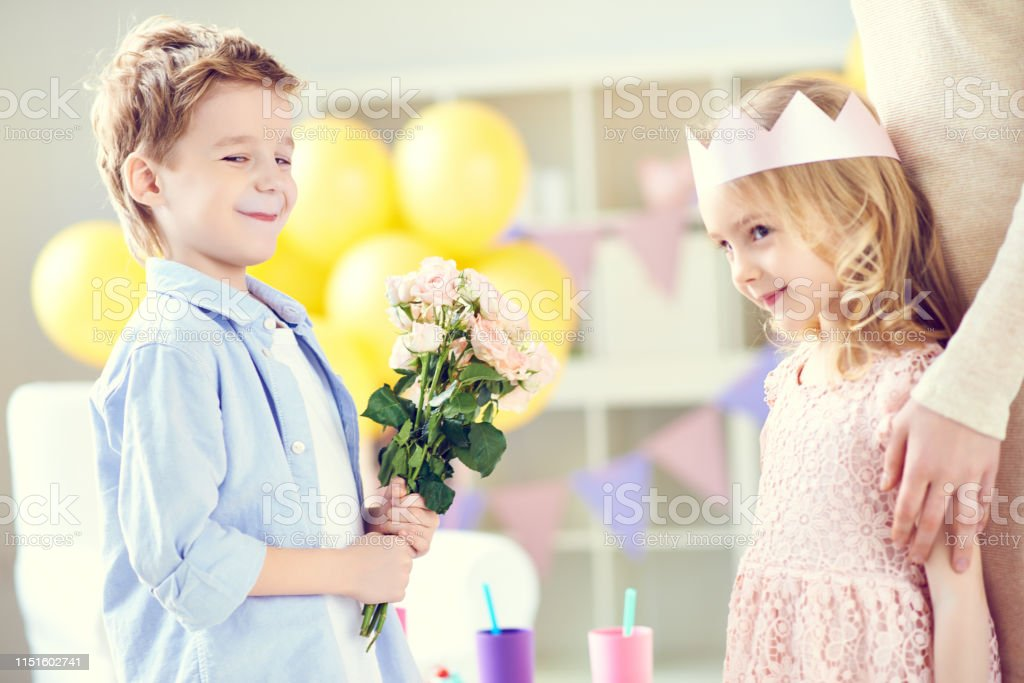 Side view of happy boy giving flowers to cute girl congratulating on...