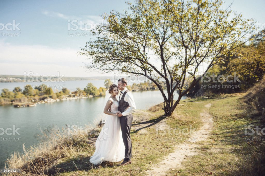 Charming bride and elegant groom on landscapes of mountains and suset at lake stock photo