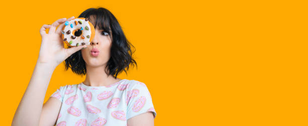 Charming brunette girl looking through a donut is feeling amazed posing on a yellow background with freespace stock photo
