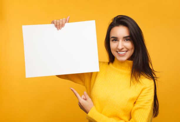 Charming brunette pointing at blank paper stock photo