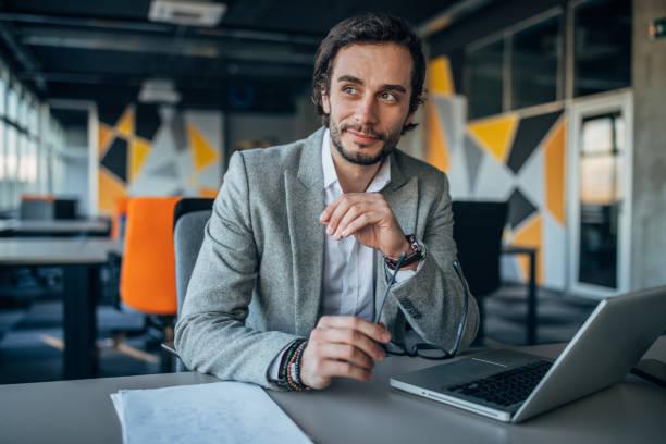 オフィスに座っている魅力的なビジネスマン - 投資家 ストックフォトと画像
