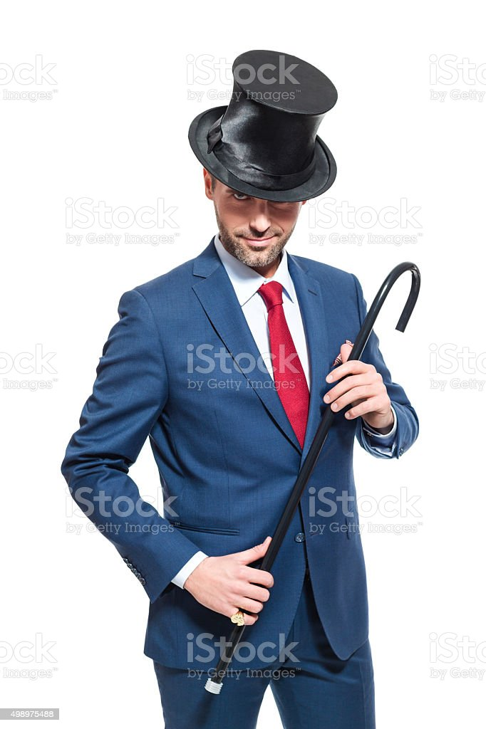 Charming businessman wearing suit and cylinder hat Portrait of elegant businessman wearing suit and cylinder hat, holding walking cane, smiling at the camera. Studio shot, one person, isolated on white. 2015 Stock Photo