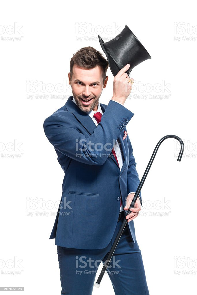 Charming businessman wearing suit and cylinder hat Portrait of elegant businessman wearing suit and cylinder hat, holding walking cane, smiling at the camera. Studio shot, one person, isolated on white. Adult Stock Photo