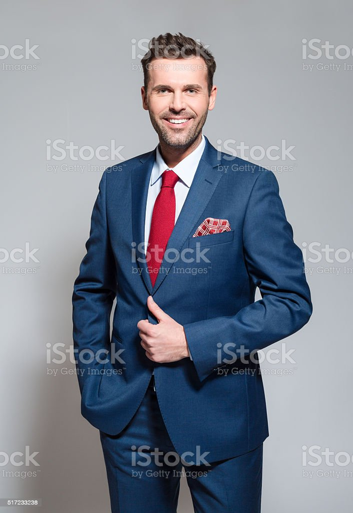 Charming businessman wearing suit, studio portrait Elegant businessman wearing suit, red tie and pocket square, standing against grey background and smiling at camera. Studio shot. Adult Stock Photo