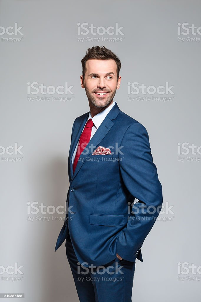 Charming businessman wearing suit, studio portrait Elegant businessman wearing suit, red tie and pocket square, standing against grey background. Studio shot, one persone. Adult Stock Photo