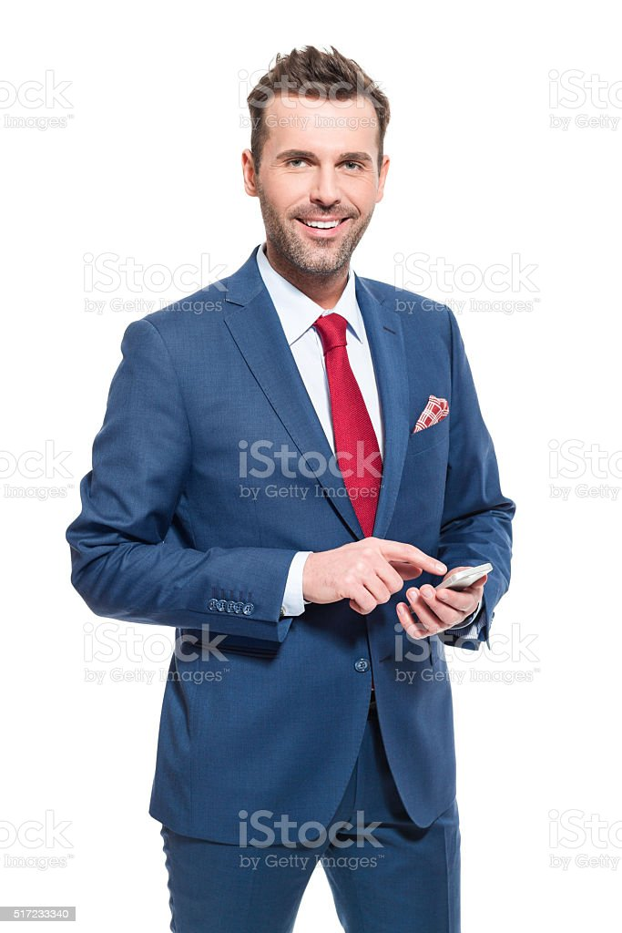 Charming businessman wearing suit, using a smart phone Elegant businessman wearing suit, red tie and pocket square, holding a smart phone in hands, smiling at camera. Studio shot, isolated on white.  Adult Stock Photo