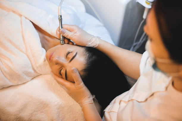 Charming caucasian brunette is having a facial spa procedure while lying with closed eyes stock photo