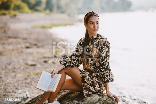 Charming caucasian brunette with headband and in floral dress sitting on rock near river, holding book and looking away.