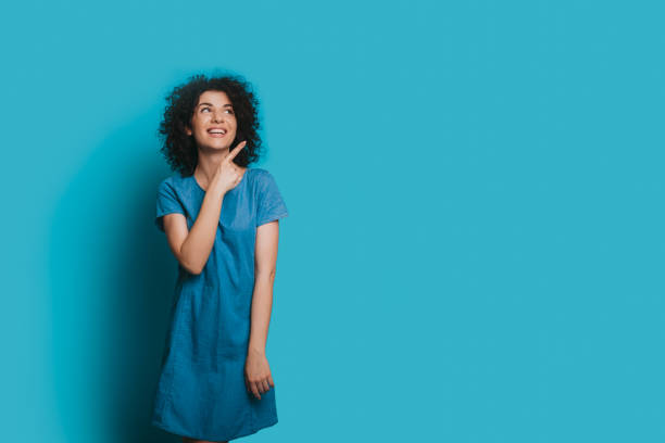 Charming caucasian woman with curly hair is posing in a blue dress and pointing to the blank space near her stock photo