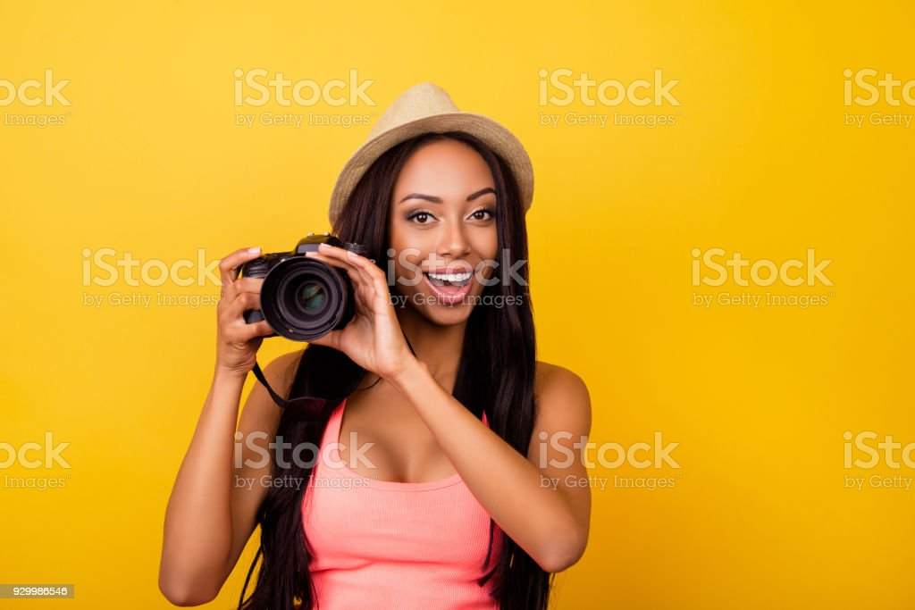 Charming cheerful dreamy afro traveller in casual outfit and beige head wear, so excited. Studio, chill, entertainment, dream, adventure, object, paparazzi concept lifestyle stock photo