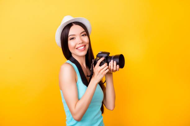 charmante chinesische teen fotograf in den sommerferien. hält sie kamera, sommer casual-outfit und einen hut tragen auf leuchtend gelbem hintergrund stellt - happy weekend bilder stock-fotos und bilder