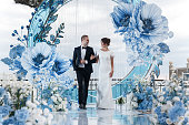 Wedding ceremony in an outdoor Banquet hall decorated with huge blue flowers. The bride and groom hold each other's hands. Banquet on the wedding day in a summer restaurant with beautiful decoration and design.Happy young couple in love