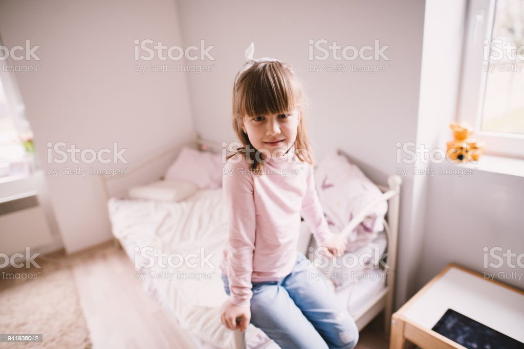 cb8e17fb4f8 Charming cute little toddler girl sitting on the edge of the bed in her  children room. - Stock image .
