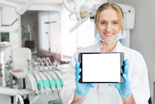 istock Charming dentist holding blank digital tablet 656179866