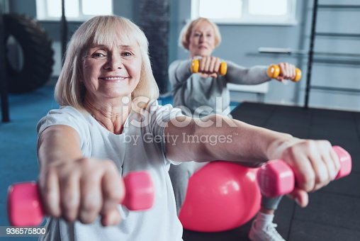 936573360 istock photo Charming elderly woman smiling for camera while lifting dumbbells 936575800
