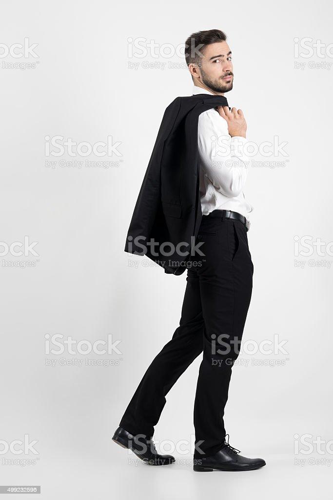 Encantador y elegante traje de Hombre caminando a llevar su chaqueta en  hombro foto de stock f5967ff50f2