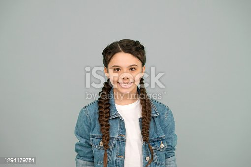 Charming face with better future. Beauty look of girl child. Happy child with long plaits grey background. Hair salon. Casual wear. Trendy fashion style. Childhood and care. Childrens day.