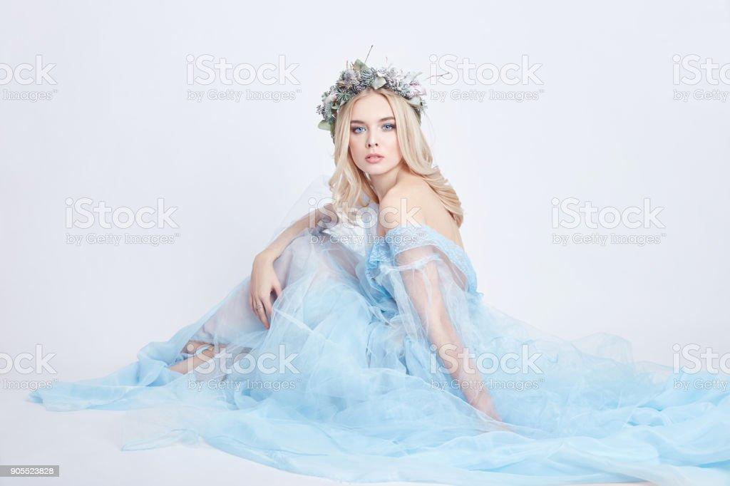 Charmante femme de fée dans une robe bleue éthérée et une couronne sur sa tête sur fond blanc, douce mystérieuse fille blonde avec une peau parfaite et le maquillage. Propreté, soins du corps et la peau photo libre de droits