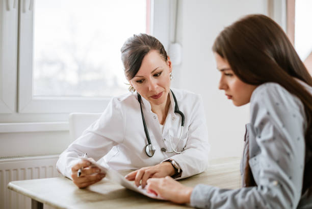 charming female doctor giving advice to a female patient. - exam stock pictures, royalty-free photos & images