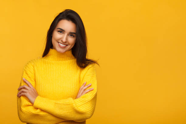 charming female on yellow backdrop - coloured background stock photos and pictures
