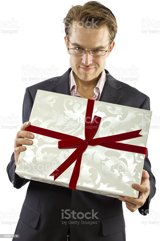 Charming Generous Boyfriend Wearing a Suit Holding a Gift stock photo