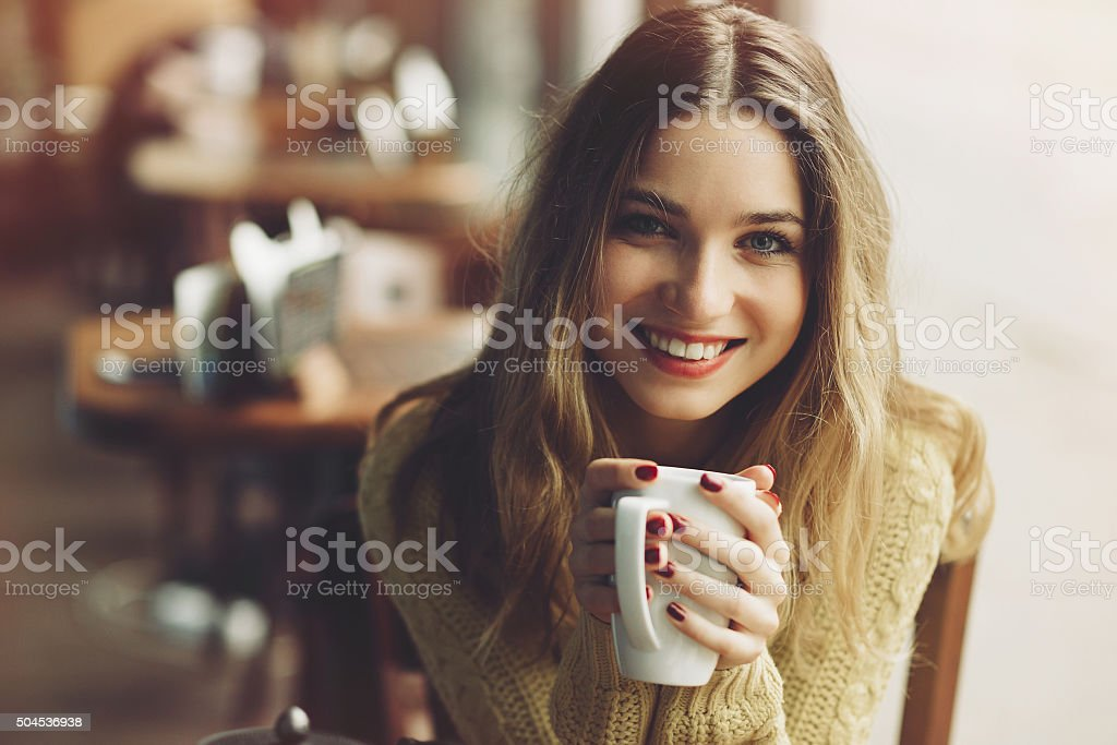 Charming girl drinking cappuccino and eating cheesecake stock photo