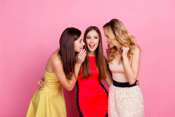Charming girl holding hand near mouth telling interesting gossips to her pretty friends who laughing, enjoying while standing over pink background, women's day, 8-march stock photo