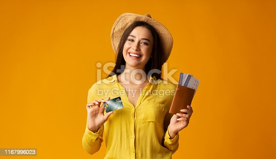 Happy Woman Holding Passport, Tickets And Credit Card On Yellow Background. Studio Shot, Free Space