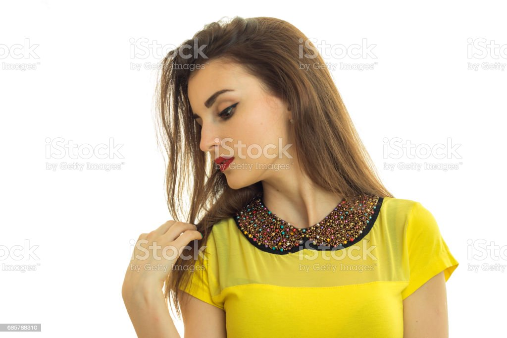 charming girl in a yellow blouse cocked her head to the side and looks down close-up stock photo