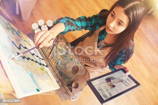 istock Charming girl painting abstract masterpiece on art canvas 854032994