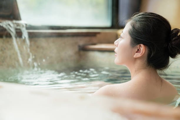 charming girl stay in hot spring water - hot spring stock photos and pictures