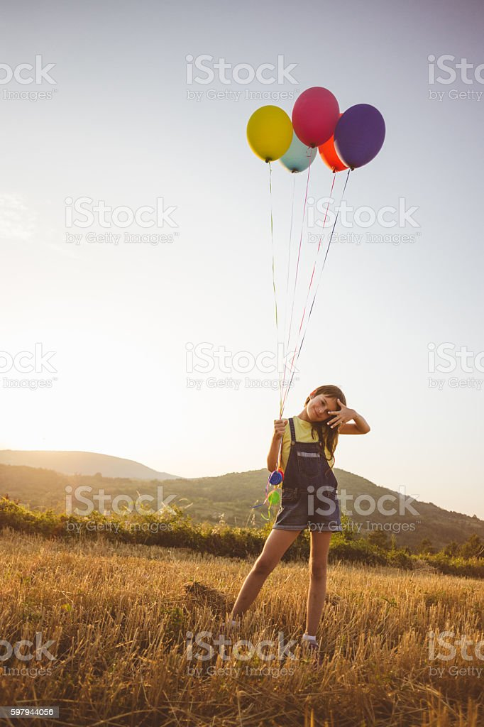 Charming girl with many balloons in the sunny countyside foto royalty-free