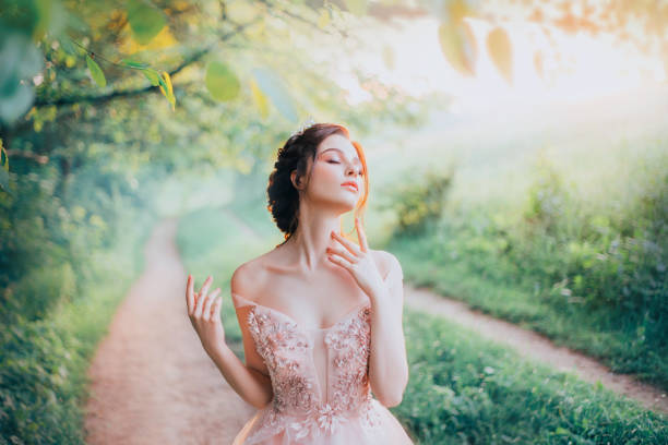 charming goddess of the spring forest stands on a narrow path and breathes in the sweet smell of nature, pleasure in motion, lady with her eyes closed strokes her beautiful neck with her fingertips - diadem stock pictures, royalty-free photos & images