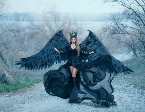 büyüleyici muhteşem koyu tanrıça kontrolleri rüzgar, hava akışı dalgaları etek ve geniş dantel kollu açık siyah elbise uzun tren, keskin boynuzları ile bayan ve gökyüzü uçmak için hazır siyah tüy kanatları - peri hayali karakter stok fotoğraflar ve resimler