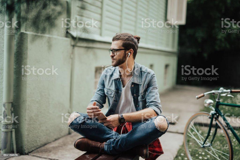 Les gars charmant vêtu d'une chemise denim utilise un smartphone à l'écoute de podcast photo libre de droits
