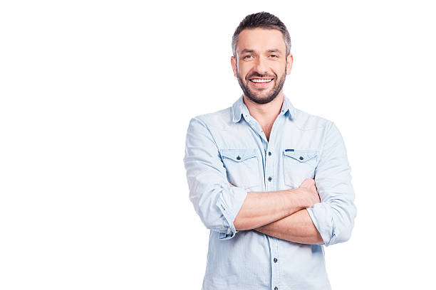 Charming handsome. Handsome young man in casual wear keeping arms crossed and smiling while standing isolated on white background arms crossed stock pictures, royalty-free photos & images