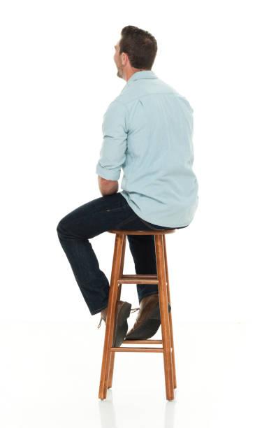 Charming happy man seated on wood stool stock photo