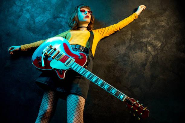 charmante hipster-frau mit lockigen haaren mit roter gitarre in neonlicht. rockmusiker spielt elektrische gitarre. 90er-jahre-konzept. - bands der 90er stock-fotos und bilder