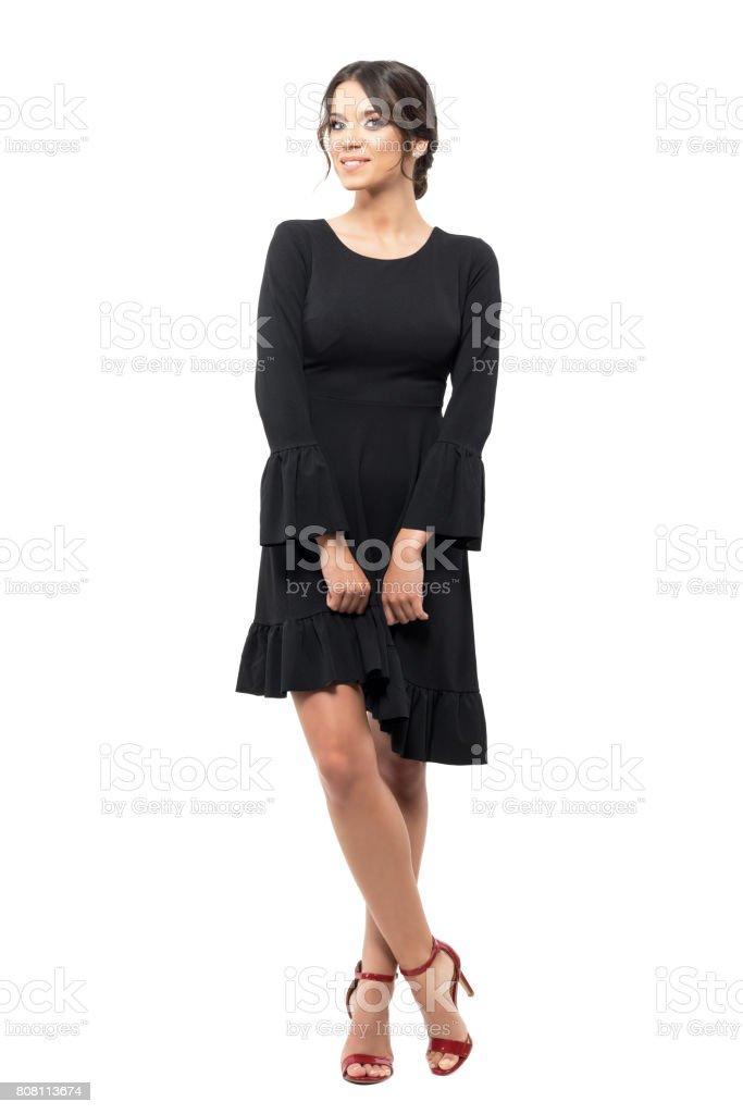 Charming Hispanic woman in black dress posing and smiling at camera stock photo