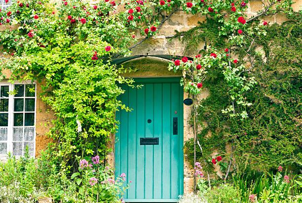charming house with green doors and red roses - kır evi stok fotoğraflar ve resimler