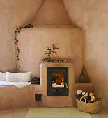 Charming inertia stove made of clay and pink plaster with lit fire and firewood basket